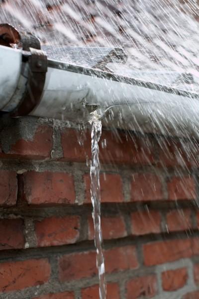 Starker-Wasserstrahl-laeuft-durch-defekte-Regenrinne