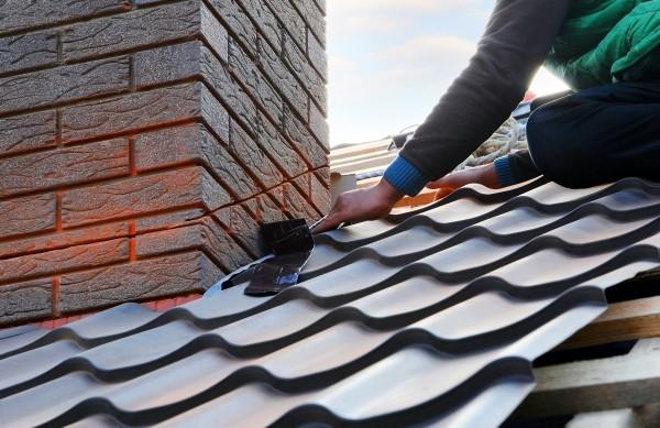 Handwerker-auf-dem-Dach-setzt-Abdichtband-ein